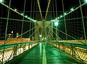 Looking along walkway on the Brooklyn Bridge at night, New York, USA