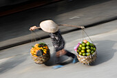 Woman carrying baskets of fruit in street, blurred motion, Hanoi, Vietnam