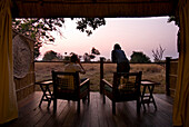 Couple looking out from room of safari lodge at dawn, South Luangwa National Park, Zambia