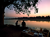 Couple sitting on log with hot drinks before dawn, South Luangwa National Park, Zambia