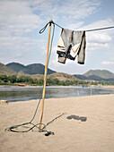 Trousers drying on washing line at shore of Mekong river, sandy beach, Luang Prabang, Laos