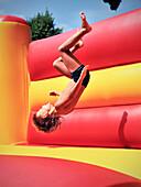 Young boy doing a somersault in a bouncy castle, Freibad Spiesel, Aalen, Schwaebische Alb, Baden-Wuerttemberg, Germany