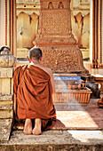 Buddhist monk praying at Pha That Luang temple, Vientiane, Laos