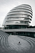 child cycling in front of City Hall, Southwark, City of London, England, UK
