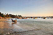 Fishers carry their small boat to the beach, fishing boats, fishing village, South China Sea, Mui Ne, Binh Thuan, Vietnam