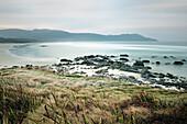 Beach with rocks and mountains, Cloudy Bay, Bruny Island, Tasmania, Australia