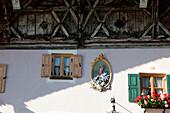 Traditionelle Hauswand mit Geranien und Heiligen Abbildung, Mittenwald, Bayern, Deutschland