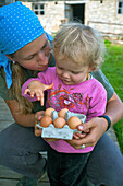 Woman and girl with fresh eggs, Hofbauern-Alm, Kampenwand, Chiemgau, Upper Bavaria, Germany