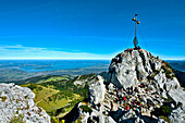 Mountaineers near summit cross, Kampenwand, lake Chiemsee in background, Chiemgau, Upper Bavaria, Germany
