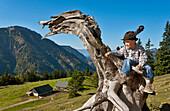 Boy sitting on a tree stub, Hofbauern-Alm, Kampenwand, Chiemgau, Upper Bavaria, Germany