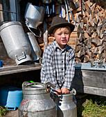 Boy holding a milk churn, Hofbauern-Alm, Kampenwand, Chiemgau, Upper Bavaria, Germany