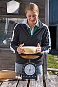 Woman weighing cheese, Hofbauern-Alm, Kampenwand, Chiemgau, Upper Bavaria, Germany