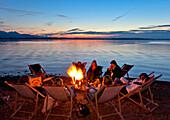 Group around a campfire, lido Uebersee, lake Chiemsee, Chiemgau, Upper Bavaria, Germany