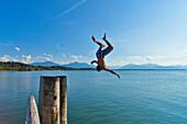 Man doing backflip into water, Chieming, lake Chiemsee, Chiemgau, Upper Bavaria, Germany