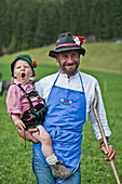 Farmer and son wearing traditional clothes, drive fromthe mountain pastures, Almabtrieb, Ulten valley, South Tyrol, Italy