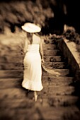 Back view of a woman in a white dress walking up a stairway, outdoors