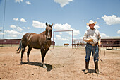 Elderly Cowboy With Horse in Corral, Texas, USA