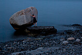 Young Woman Pushing Against Large Rock in Water, Bar Harbor, Maine, USA