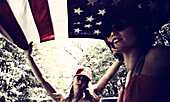 Two Young Women Underneath American Flag in Back of Pickup Truck