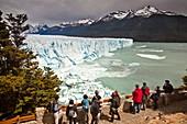 Tourists view Perito Moreno glacier front from platform, Parque Nacional Los Glaciares, Patagonia, Argentina