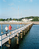 Couple running along a pier at the Baltic Sea, Hotel in background, Travemuende, Luebeck, Schleswig-Holstein, Germany