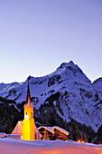 Beleuchtete Kirche vor Bergkulisse, Schröcken, Vorarlberg, Österreich