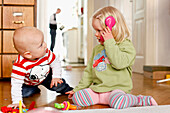 Little boy and girl playing together with a telephone, children at home, boy 9 months old, girl two years old, MR, Leipzig, Saxony, Germany