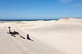 Three hikers sitting on the dunes, view towards the sea, Dunes of Leba, UNESCO World Biosphere Reserve, Slowinski National Park, Polish Baltic Sea coast, Leba, Pomeranian, Poland
