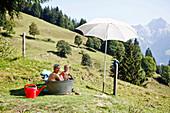 Mutter und kleiner Sohn sitzen in einer Badewanne auf der Wiese, Alpenpanorama, Steinernes Meer, Salzburger Land, MR, Maria Alm, Salzburg, Österreich
