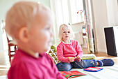 Two little girls playing in the living room with books, girls aged 2 and 5 years old, MR, Leipzig, Sachsen, Germany