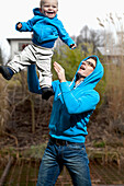 Father playing with his son in the garden, throwing him in the air, both wearing blue shirts, boy 18 months old, MR, Bad Oeynhausen, North Rhine-Westphalia, Germany
