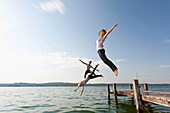 young people jump from pier into Lake Starnberg, Bavaria, Germany