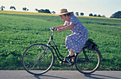 Elderly woman riding a bicycle, Upper Bavaria, Germany