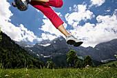 Jogger girl jumping on meadow, Eng, Ahornboden, Karwendel mountains, Tirol, Austria, Europe
