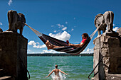 Young woman jumping into the water, man reading in hammock, Lake Starnberg, Upper Bavaria, Germany, Europe