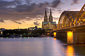 View over Rhine river in the evening light to Cologne Cathedral and Hohenzollern Bridge, Cologne, North Rhine-Westphalia, Germany