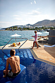 Man and woman at the pool and on the deck of the Yachting Club Villas, Elounda Beach Resort, Elounda, Crete, Greece