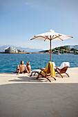 Couple sunbathing on the terrace of the Yachting Club,  Beach Resort, Elounda, Crete, Greece