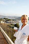 Frau im Bademantel morgens am Pool mit Kaffeetasse, Elounda Beach Resort, Elounda, Kreta, Griechenland