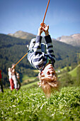 Boy hanging upside down on a rope during a hike, Pflersch, Gossensass, South Tyrol, Italy