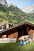 Children sitting in front of a hut while carving, Gossensass, Brenner, South Tyrol, Trentino-Alto Adige/Suedtirol, Italy