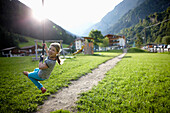 Girl playing on the zip line, outdoor area of the Hotel, Pflersch, Gossensass, South Tyrol, Italy