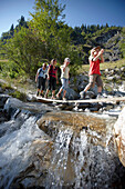 Family crossing a stream, family hike,  Pflersch, Gossensass, South Tyrol, Italy