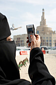 Woman photographing KDF Islamic Center with mobile phone, Doha, Qatar