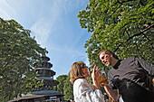 People enjoying a sunny day at the Chinesischer Turm beer garden, Englischer Garten, Munich, Upper Bavaria, Bavaria, Germany, Europe