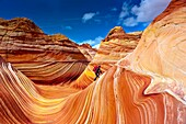 Hiker exploring ´The Wave´, a 190 million year old Jurassic-age Navajo sandstone rock formation, Coyotte Buttes, Paria Canyon-Vermillion Cliffs Wilderness Area, Utah-Arizona border, USA