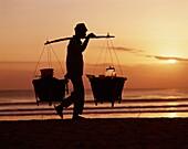 Bali, Balinese, beach, buckets, carry, carrying, ca. Bali, Asia, Balinese, Beach, Buckets, Carry, Carrying, Catch, Evening, Fisherman, Holiday, Indonesia, Indonesian, Kuta, Landmark