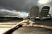 A dramatic scene where a dragonfly is perched on a rope which is on a wharf that has 2 lounge chairs