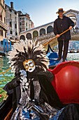 A masked woman during carnival in a gondola on the Canale Grande, Venice, Italy, Europe