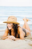 Portrait of a beautiful brunette woman at the beach with a bikini and a hat